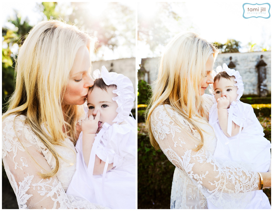 Mother kissing baby at a Baptism at Spanish Monastery in Miami.